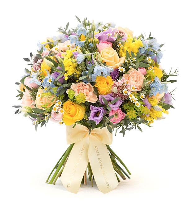 Bouquet of delphiniums, peach roses, scented mimosa and pink ranunculus