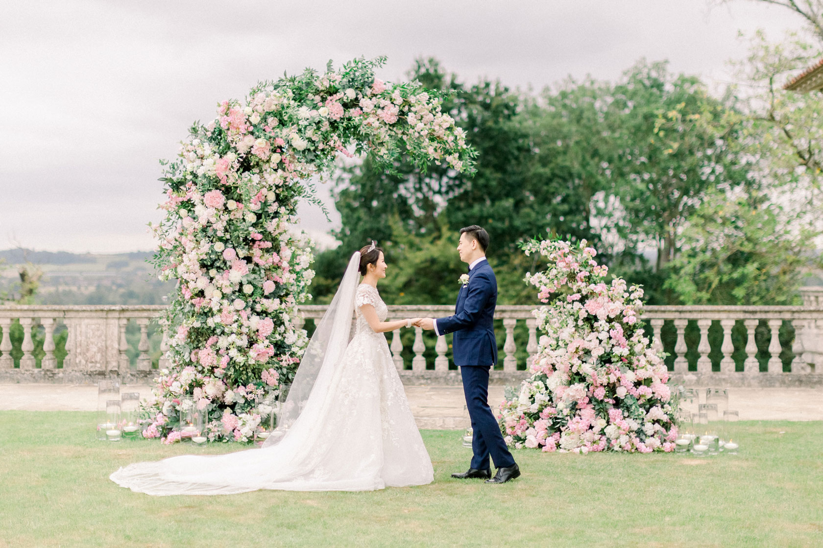 A Chinese bride and groom outside at Cliveden House getting married in front of a flower arch