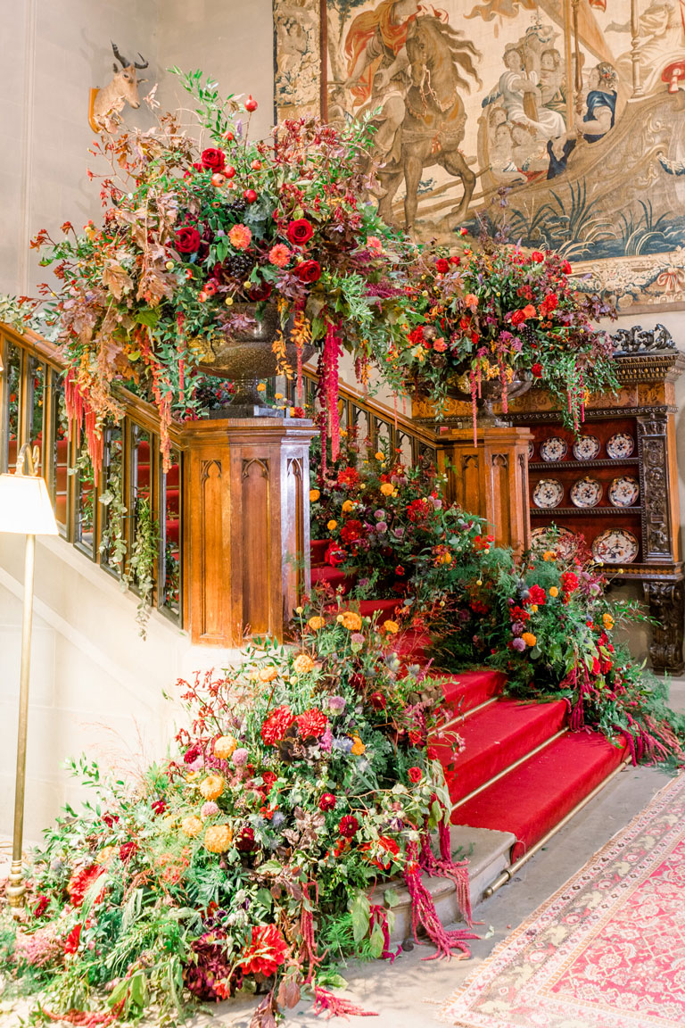 huge floral urns and cascading blooms falling down the carpeted steps of the grand staircase inside the castle