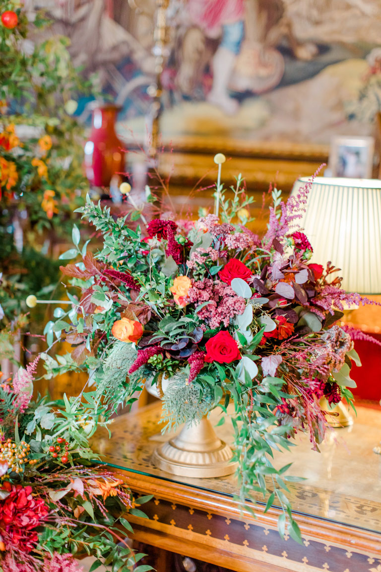 table flowers of oranges, browns, rich reds in a gold urn