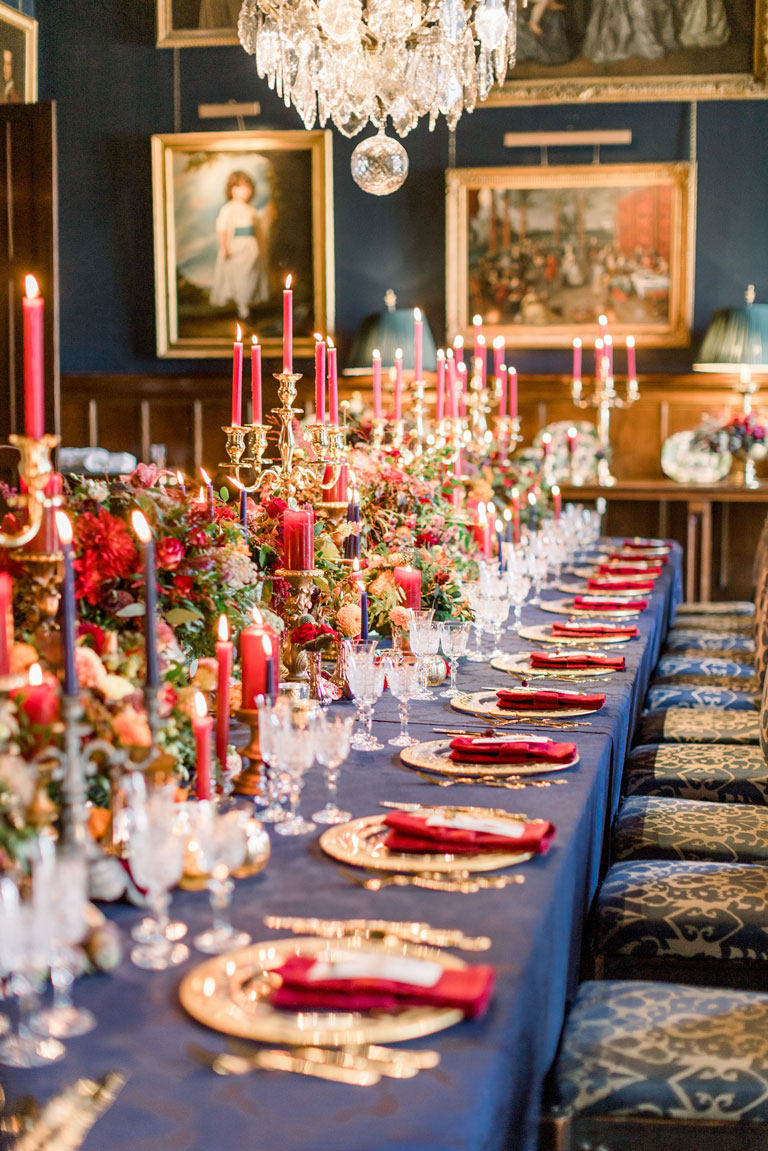 eastnor castle regal ornate navy and gold wedding breakfast with red candles, gold plates
