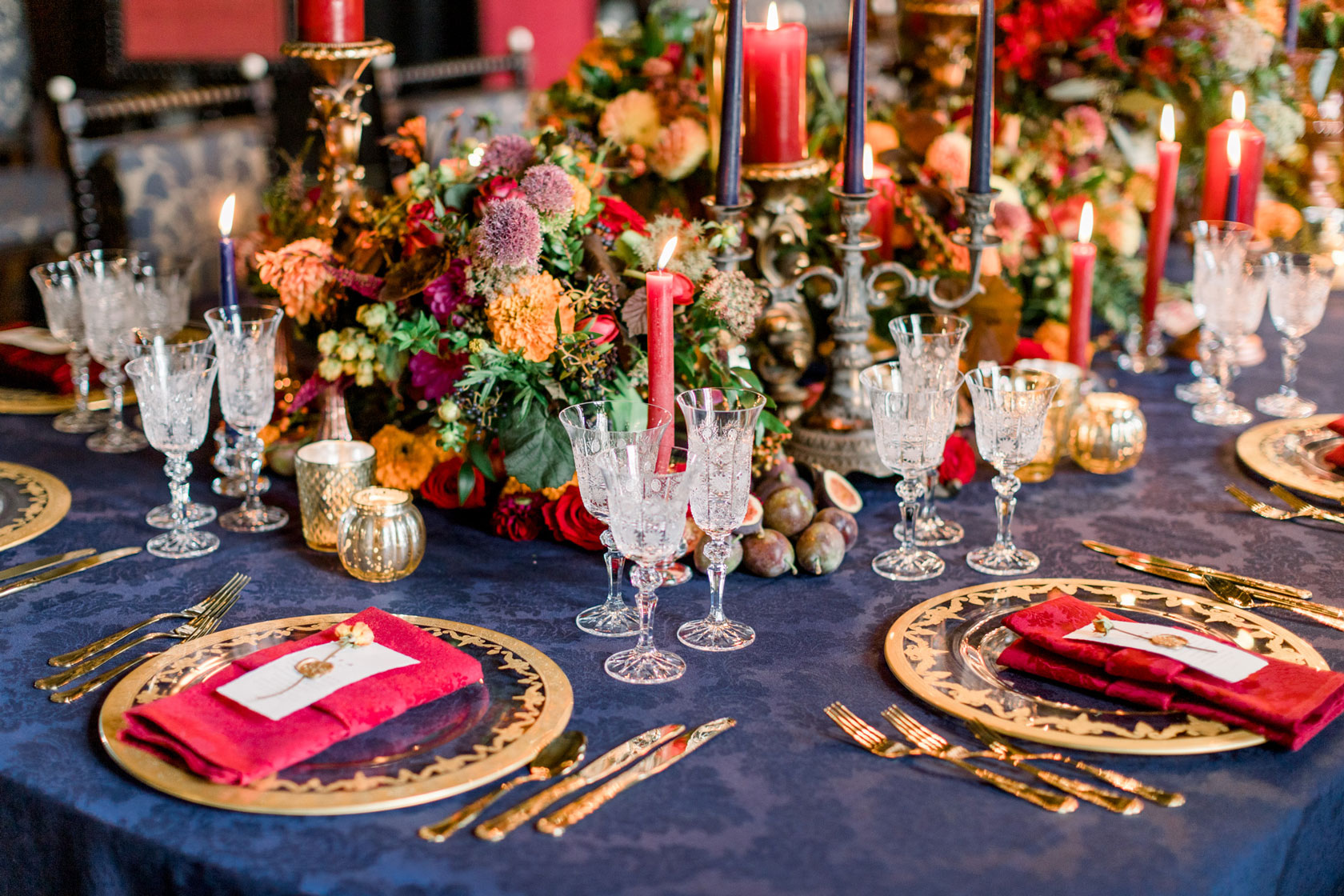 navy linen, gold charger plates and cutlery, red napkins and delicate crystal glasses