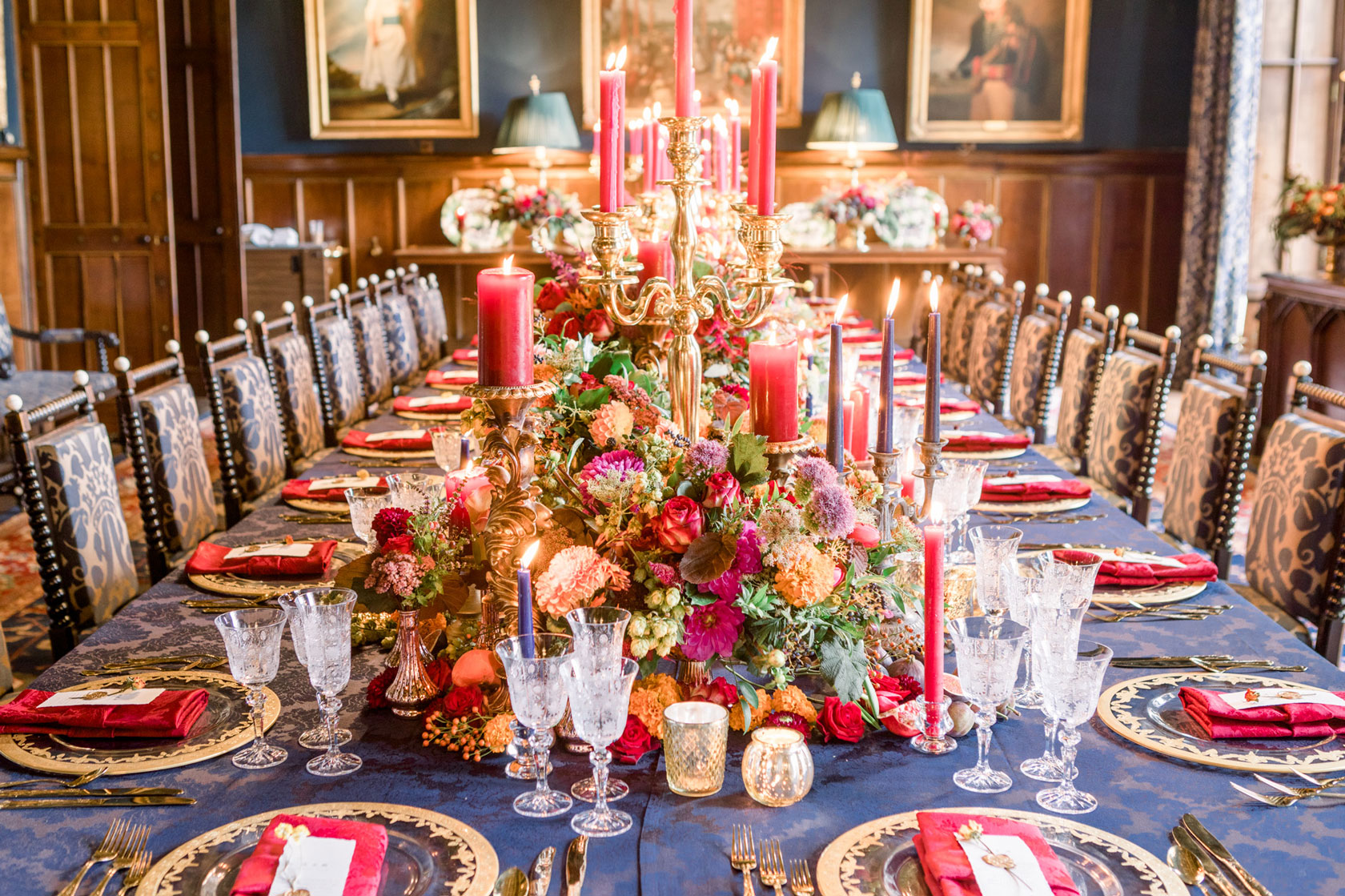 a long table regal inspired wedding brekfast table in a castle with navy linen, gold charger plates and cutlery, gold candelabras with red candles