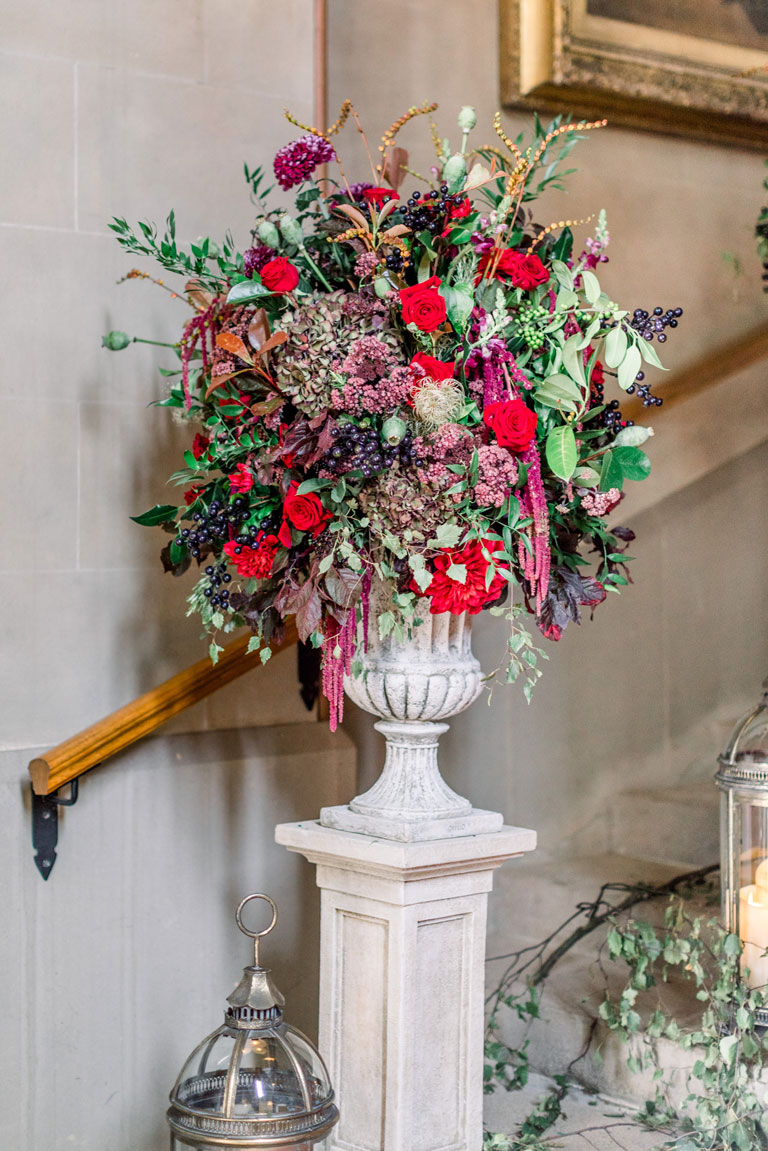 a white stone plynth with huge urns of red and green flowers