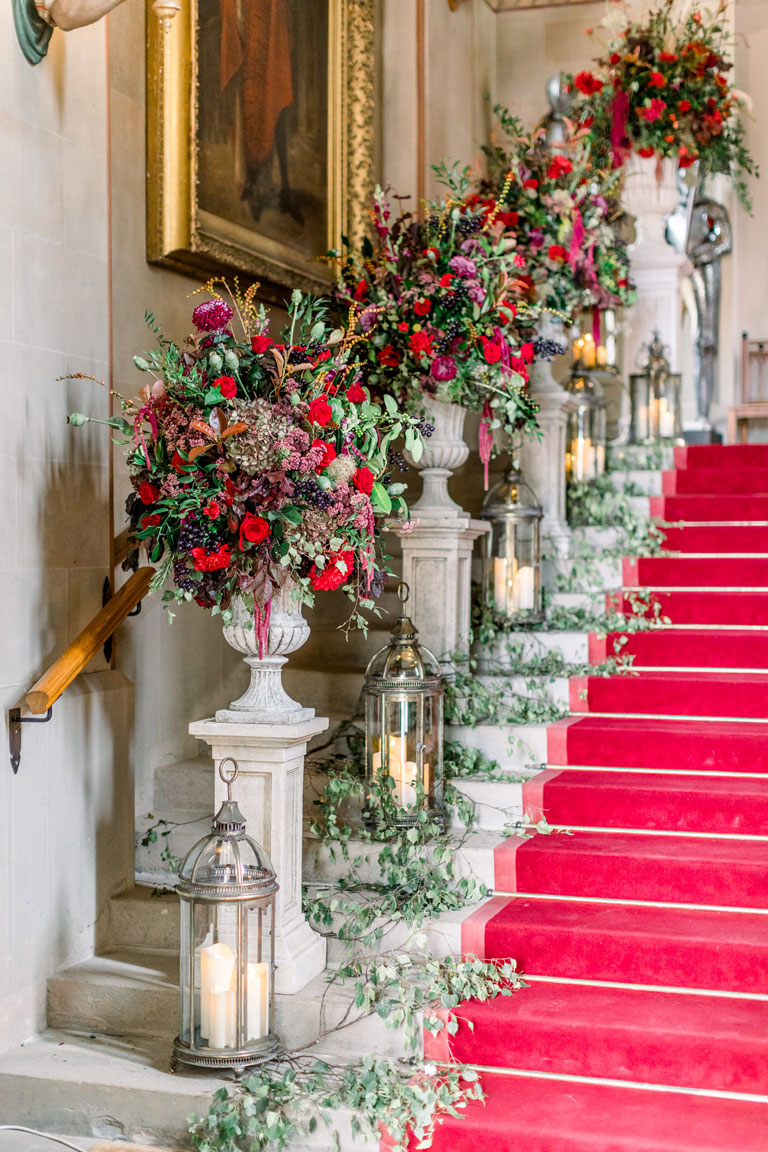 a castle staircase with a red carpet and plynths of regal flowers on each step