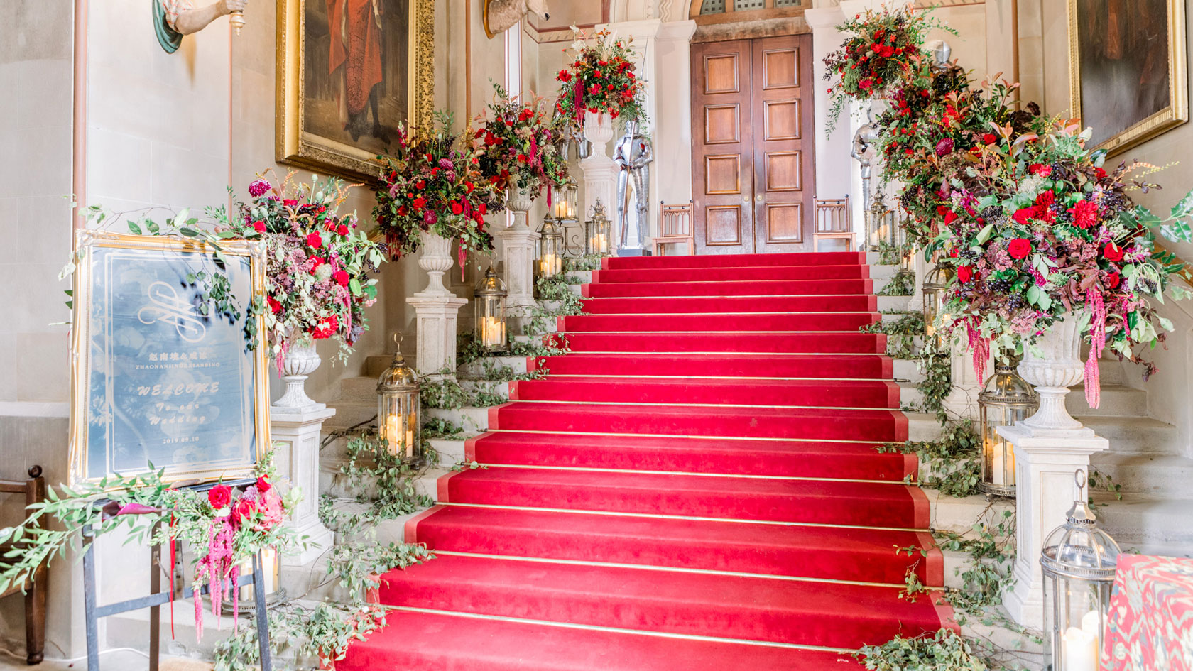 a castle staircase with an avenue or urns and plynths filled with flowers on each step