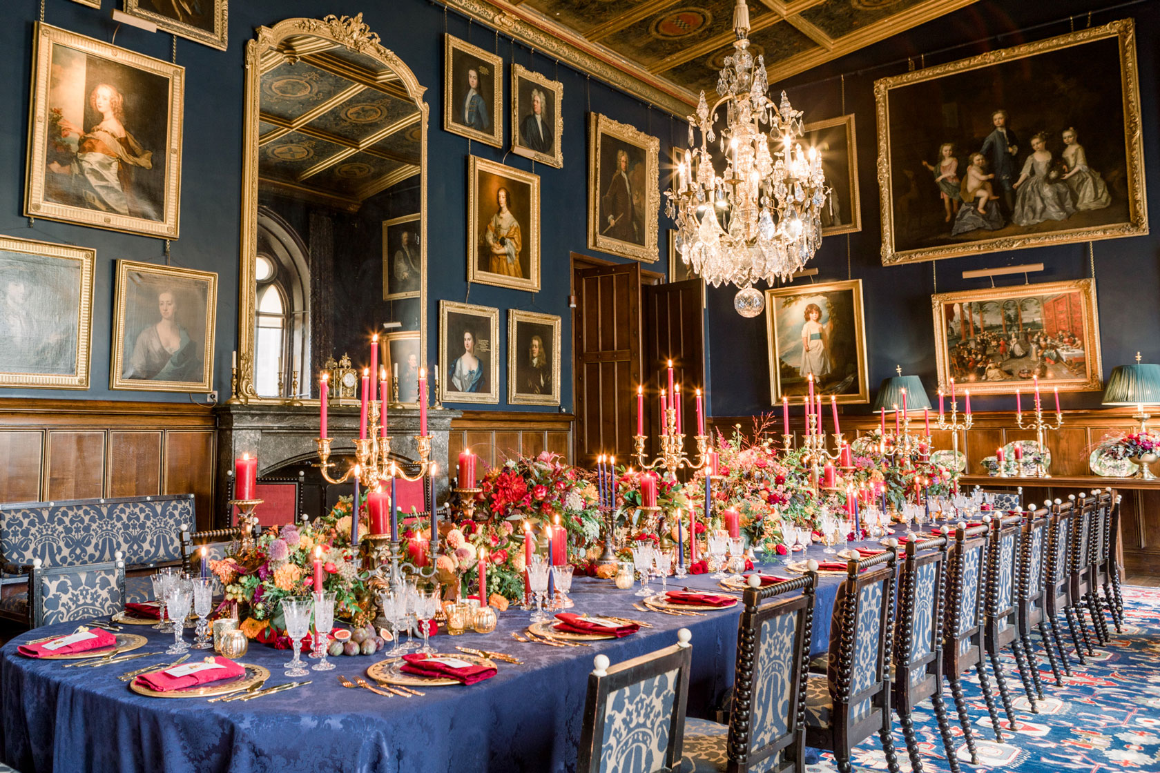 navy and gold regal inspired castle wedding breakfast banquet with hundreds of candles, gold chalices of flowers inside a castle