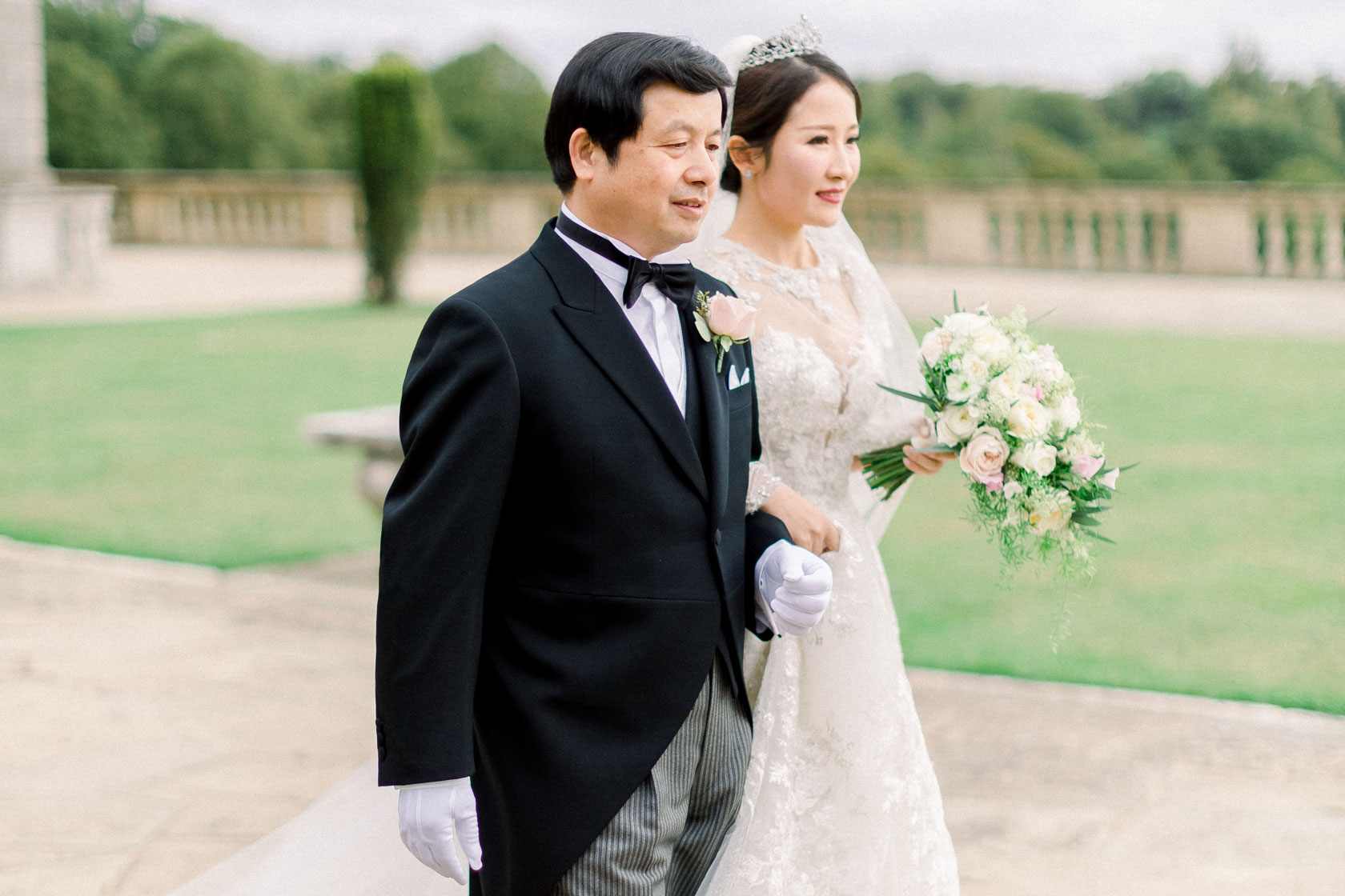 Chinese bride with her Father walking down the aisle with her bridal bouquet on the lawn at Cliveden House